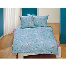 Linge de lit avec rameaux de cerisiers en fleur sur fond couleur acqua