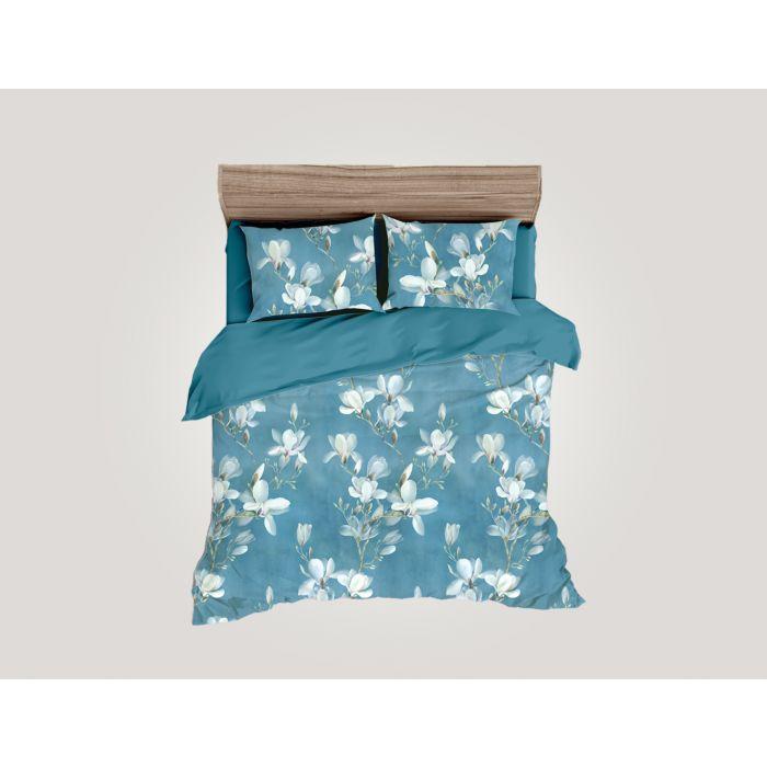 Linge de lit dans un beau ton bleu avec fleurs de magnolia blanches
